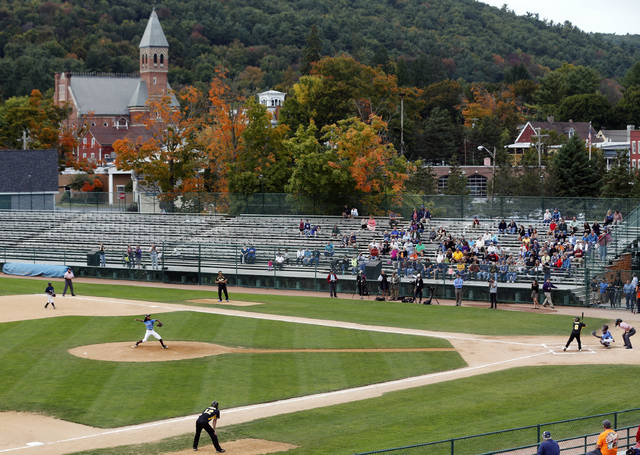 FILE - In this Sept. 25, 2014, file photo, an exhibition baseball game is played at Doubleday Field in downtown Cooperstown, N.Y., near the National Baseball Hall of Fame. There's much more to the one-stoplight village than its No. 1 attraction, but the National Baseball Hall of Fame on Main Street is truly a great shrine for the game, and even if you don't have a player to root for you can check out a game at Doubleday Field or at any of the 20-plus fields a few miles away at Cooperstown Dreams Park. (AP Photo/Mike Groll, File)