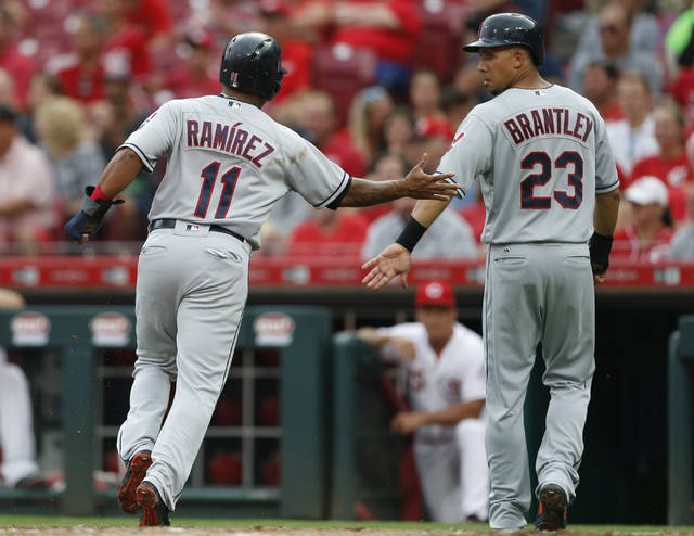 Cleveland Indians' Jose Ramirez (11) and Michael Brantley (23) celebrate after scoring on Yonder Alonso single off Cincinnati Reds starting pitcher Sal Romano during the first inning of a baseball game, Tuesday, Aug. 14, 2018, in Cincinnati. (AP Photo/Gary Landers)