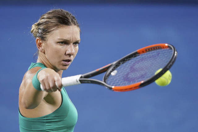 Simona Halep, of Romania, prepares to serve to Ajla Tomljanovic, of Australia, during the Western & Southern Open tennis tournament Wednesday, Aug. 15, 2018, in Mason, Ohio. (AP Photo/John Minchillo)