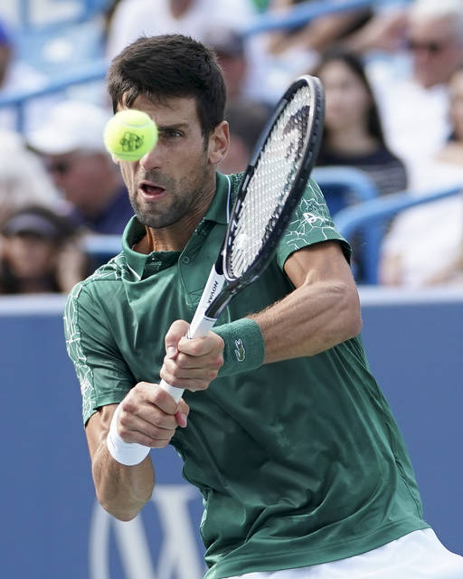 Novak Djokovic, of Serbia, returns Milos Raonic, of Canada, at the Western & Southern Open tennis tournament, Friday, Aug. 17, 2018, in Mason, Ohio. (AP Photo/John Minchillo)