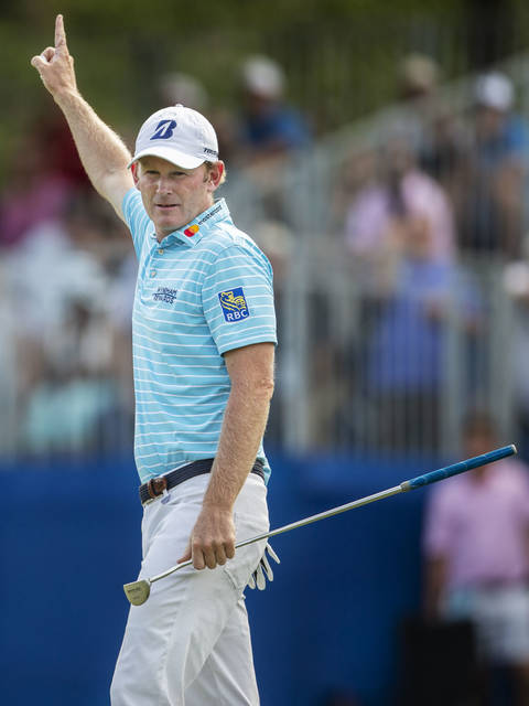 Brandt Snedeker raises his arm after sinking an eagle putt on the 15th hole during the second round of the Wyndham Championship golf tournament at Sedgefield Country Club in Greensboro, N.C., Friday, Aug. 17, 2018. (Khadejeh Nikouyeh/News & Record via AP)