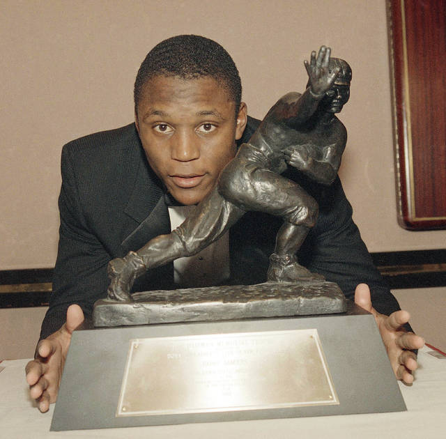 FILE - In this Dec. 8, 1988, file photo, Oklahoma State's running back Barry Sanders poses with his Heisman Trophy at New York's Marriott Marquis Hotel. His rare combination of exceptional power, speed and elusiveness helped him run for at least two touchdowns in every game that season and at least four on seven occasions. (AP Photo/Susan Ragan, File)