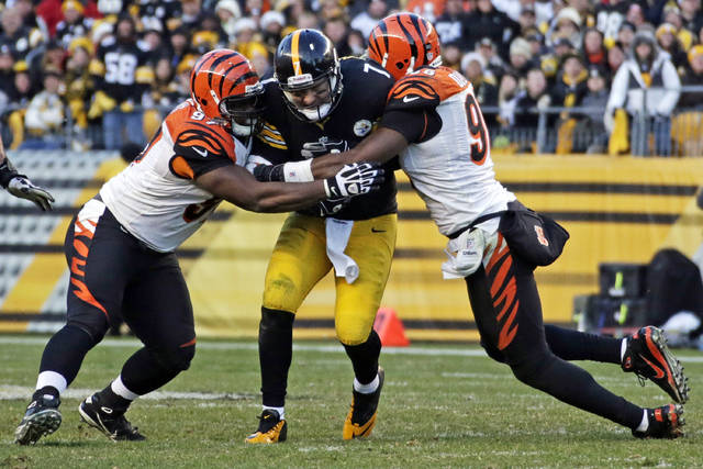 FILE - This Dec. 23, 2012 file photo shows Pittsburgh Steelers quarterback Ben Roethlisberger (7) being tackled after a 4-yard scramble, by Cincinnati Bengals defensive tackle Geno Atkins, left, and defensive end Carlos Dunlap during the fourth quarter of an NFL football game in Pittsburgh. The Bengals have agreed to contract extensions with defensive tackle Geno Atkins and end Carlos Dunlap, who were entering the final years on their deals, Tuesday, Aug. 28, 2018. (AP Photo/Gene J. Puskar, File)