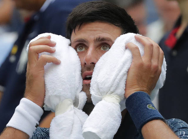 Novak Djokovic, of Serbia, puts an ice towel to his face during a changeover in his match against Marton Fucsovics, of Hungary, during the first round of the U.S. Open tennis tournament, Tuesday, Aug. 28, 2018, in New York. (AP Photo/Frank Franklin II)