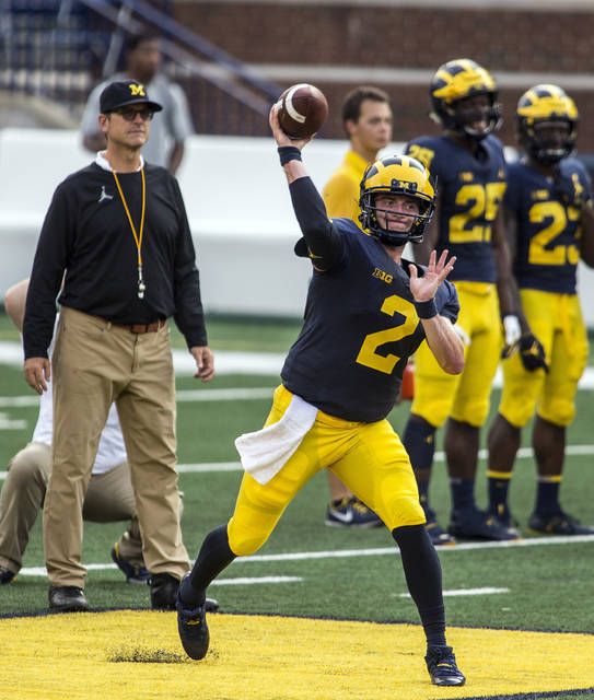 Michigan quarterback Shea Patterson (2) throws a pass while watched by head coach Jim Harbaugh, left, during a preseason open practice session by the NCAA college football team at Michigan Stadium in Ann Arbor, Mich., Sunday, Aug. 26, 2018. Patterson is a transfer from Mississippi and has been named the starter by Harbaugh. (AP Photo/Tony Ding)