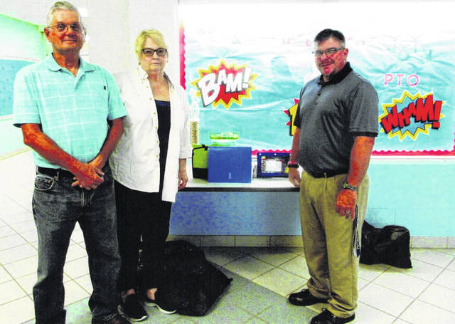 From left, Don Spurling and Judy Stapler of Dems for Kids are with Putman Elementary School Principal Robert Bandow as they drop off school supplies. Twice each year since 2001, the Dems for Kids program of the Clinton County Democratic Party has donated school supplies to all public elementary schools.