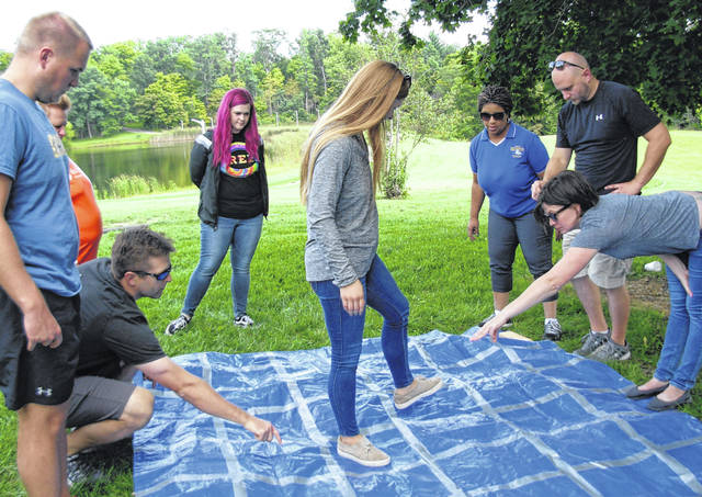 Emily Osborne (center) navigates through a team-building exercise with a little help from her new LC friends including, clockwise from left, Dalton Wood, Lance Beus, Melissa Puckett, Zanna Haines, Jeanne Pope, Josh Martin and Marian Miller.