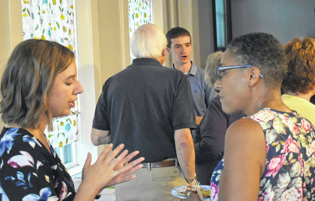 Locals got a chance to see and hear about the projects the Clinton Community Fellows have been working on during their summer breaks at an open house on Tuesday. In the left foreground is Bethany Brausch, and in the center background facing the camera is Ty Snarr.
