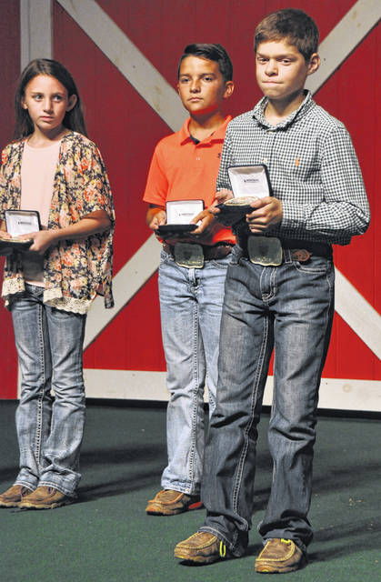 Jaden Snyder of the Wilmington area, right foreground, earns a belt buckle at the Ohio State Fair.