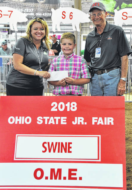 Wade Smith, center, is recognized at the Ohio State Fair as an Outstanding Market Exhibitor (OME) in swine.