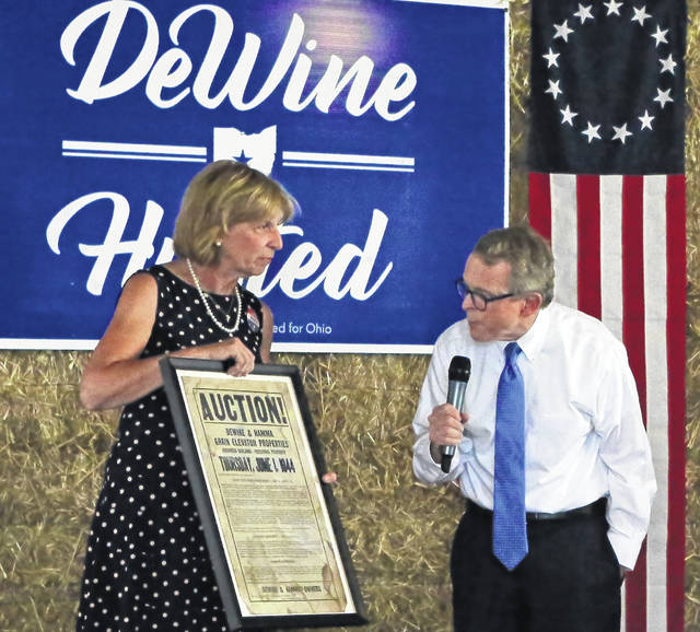 Mike and Fran DeWine eye an old auction flyer for his family's DeWine and Hamma Grain Elevator in Sabina.