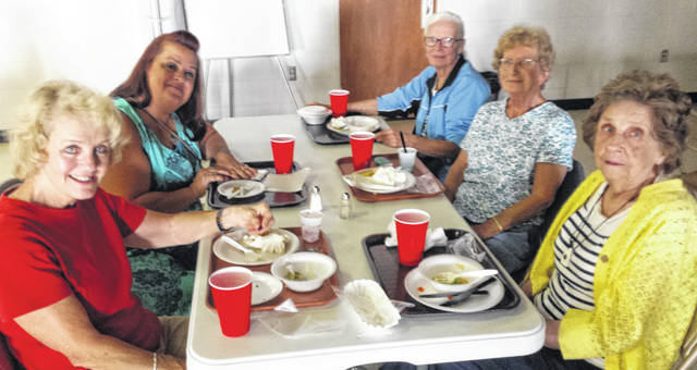 Some local residents enjoy the community dinner at Grace UMC Thursday.