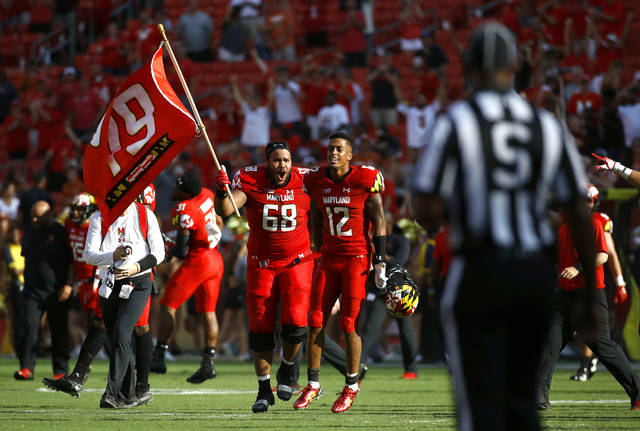 Maryland offensive lineman Ellis McKennie (68) walks with teammate Taivon Jacobs as he waves a flag in remembrance of offensive lineman Jordan McNair, who died after collapsing on a practice field during a spring practice, after an NCAA college football game against Texas, Saturday, Sept. 1, 2018, in Landover, Md. Maryland won 34-29. (AP Photo/Patrick Semansky)
