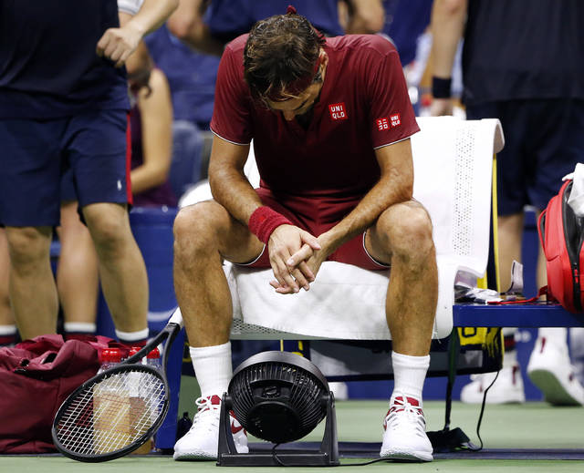 Roger Federer, of Switzerland, sits in front of a fan during a changeover in his match against John Millman, of Australia, during the fourth round of the U.S. Open tennis tournament early Tuesday, Sept. 4, 2018, in New York. (AP Photo/Jason DeCrow)