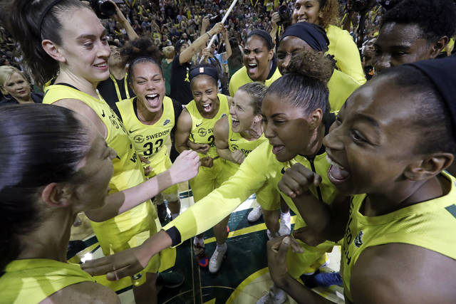 Seattle Storm players gather in a celebratory huddle after a 94-84 win over the Phoenix Mercury during Game 5 of a WNBA basketball playoff semifinal, Tuesday, Sept. 4, 2018, in Seattle. The Storm advanced to the WNBA finals. (AP Photo/Elaine Thompson)