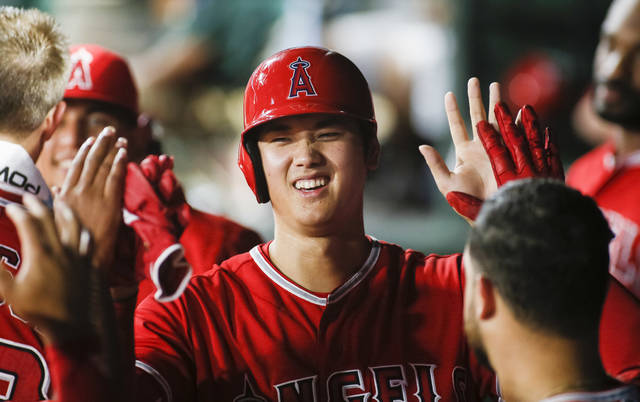 Los Angeles Angels' Shohei Ohtani smiles as he is greeted in the dugout by teammates after scoring on a single by Andrelton Simmons against the Texas Rangers during the seventh inning of a baseball game Wednesday, Sept. 5, 2018, in Arlington, Texas. (AP Photo/Ray Carlin)