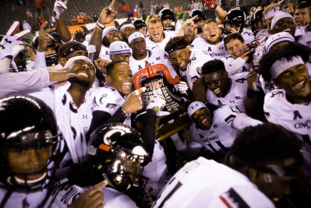 Cincinnati players pose with the bell after defeating Miami of Ohio 21-0 during an NCAA college football game Saturday, Sept. 8, 2018, in Cincinnati. (Albert Cesare/The Cincinnati Enquirer via AP)