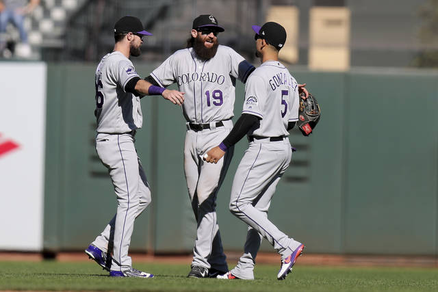 Colorado Rockies left fielder David Dahl (26), center fielder Charlie Blackmon (19) and right fielder Carlos Gonzalez (5) celebrate a victory over the San Francisco Giants after a baseball game in San Francisco, Sunday, Sept. 16, 2018. (AP Photo/Scot Tucker)