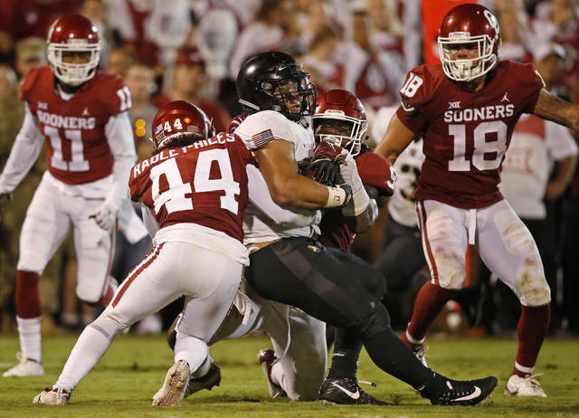 Army running back Darnell Woolfolk, center, is brought down by Oklahoma defensive back Brendan Radley-Hiles (44) and linebacker Kenneth Murray, right, in the second half of an NCAA college football game in Norman, Okla., Saturday, Sept. 22, 2018. Oklahoma won 28-21 in overtime. Murray had a school-record 28 tackles. (AP Photo/Sue Ogrocki)