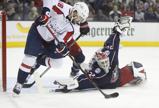 FILE - In this April 19, 2018, file photo, Columbus Blue Jackets' Sergei Bobrovsky, right, of Russia, makes a save against Washington Capitals' Chandler Stephenson during Game 4 of an NHL first-round hockey playoff series in Columbus, Ohio. Bobrovsky and forward Artemi Panarin are the best players on the team and part of the reason the Blue Jackets will be solid playoff contenders again this season. (AP Photo/Jay LaPrete, File)