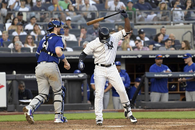 "FILE - In this Saturday, Sept. 15, 2018 file photo, New York Yankees' Andrew McCutchen reacts after striking out to end the seventh inning of a baseball game as Toronto Blue Jays catcher Danny Jansen, left, heads off the field at Yankee Stadium in New York. The most-heard sound at major league ballparks this year was ""Strike three!"" Strikeouts will exceed hits over a full season for the first time in major league history. (AP Photo/Bill Kostroun, File)"