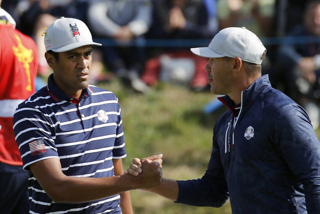Tony Finau of the US, left, and his teammate Brooks Koepka congratulate each other on the 15th during their fourball match against Europe players Justin Rose and Jon Rahm on the opening day of the 42nd Ryder Cup at Le Golf National in Saint-Quentin-en-Yvelines, outside Paris, France, Friday, Sept. 28, 2018. (AP Photo/Francois Mori)