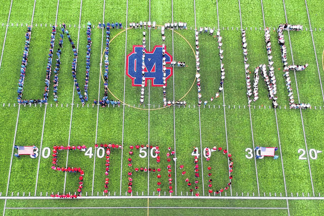 "Each year Clinton-Massie Local Schools takes a moment to remember those lost in the 9/11 attacks. The school district celebrates their lives through activities on Patriot Day, as well as taking time to reflect on those in the students' own lives they have lost. This year the high school was the participating school for the on-field activity. Each class was assigned a color: seniors/white, juniors/blue, sophomores/red, freshmen/white and the staff wore blue. As usual, the students were respectful while C-M Superintendent Matt Baker addressed the crowd. They were also patient and flexible during the setup process. Participants spelled out the words ""United We Stand"". There were also activities in each of the other buildings commemorating the day."