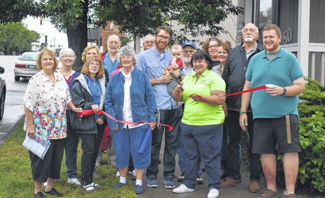 Rhonda Wheasler cuts the ribbon on Saturday at the new location of the Clinton County Democratic Party headquarters, now located on South Mulberry Street in Wilmington.