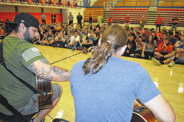 "In the foreground from left are Marine Corps veteran Sal Gonzales and singer and U.S. Navy veteran Jason Michael Carroll. Both of them performed a song for an assembly of the eighth-grade class at Wilmington Middle School. The veterans shared wisdom with the young students, including a comment that ""everybody here will have trauma in this life."""