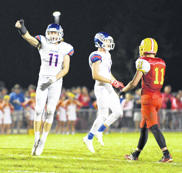 Clinton-Massie's Tate Olberding (11) and Corey May (1) celebrate on defense during Friday night's game against Fenwick.