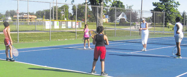 Cathy Fay taught four girls about playing tennis as part of Harvest of Gold's 2018 summer camp.