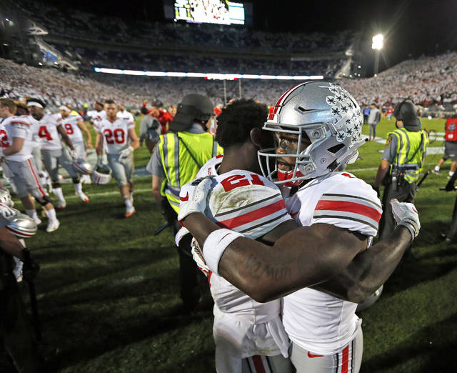 Ohio State's Paris Campbell (21), and Johnnie Dixon (1) embrace after beating Penn State 27-26 in an NCAA college football game in State College, Pa., Saturday, Sept. 29, 2018. (AP Photo/Chris Knight)