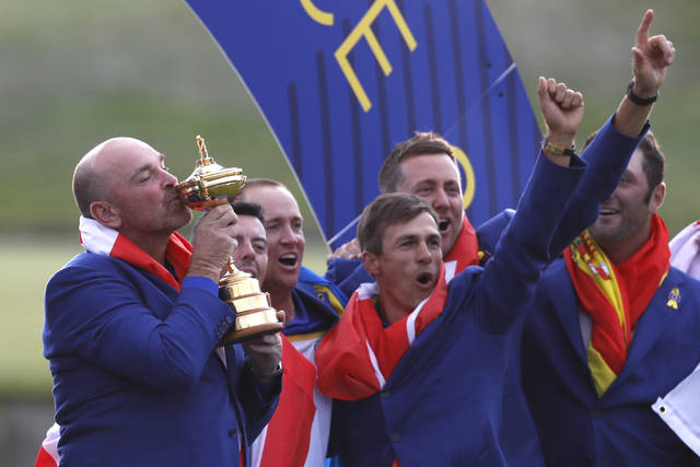 Europe team captain Thomas Bjorn kisses the cup as he celebrates with his players after the European team won the 2018 Ryder Cup golf tournament at Le Golf National in Saint Quentin-en-Yvelines, outside Paris, France, Sunday, Sept. 30, 2018. (AP Photo/Alastair Grant)