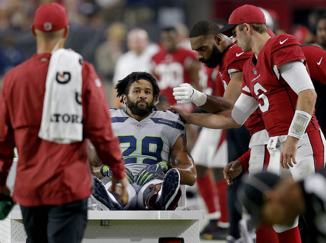 Seattle Seahawks defensive back Earl Thomas (29) is greeted by Arizona Cardinals players as he leaves the field after breaking his leg during the second half of an NFL football game, Sunday, Sept. 30, 2018, in Glendale, Ariz. The Seahawks won 20-17. (AP Photo/Ross D. Franklin)
