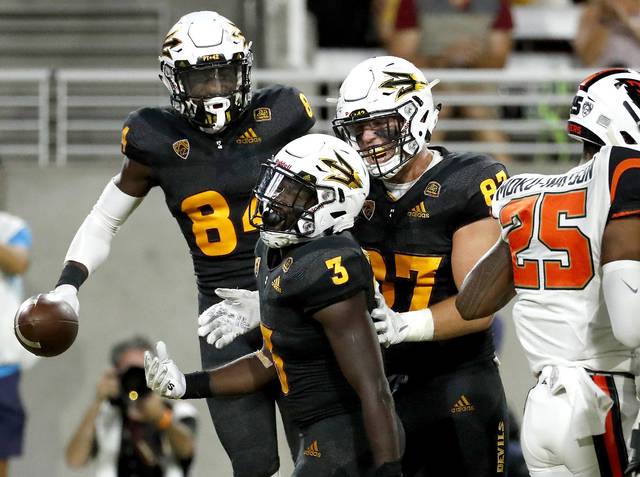 Arizona State running back Eno Benjamin (3) celebrates his touchdown with tight end Tommy Hudson, right, and wide receiver Tyerell Baldonado-Kaeiopu (84) during the second half of an NCAA college football game against Oregon State, Saturday, Sept. 29, 2018, in Tempe, Ariz. (AP Photo/Matt York)