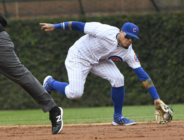 Chicago Cubs shortstop Javier Baez (9) fields a ball hit by Milwaukee Brewers' Lorenzo Cain (6) during the third inning of a tie break baseball game on Monday, Oct. 1, 2018, in Chicago. Baez threw to first for the out. (AP Photo/Matt Marton)