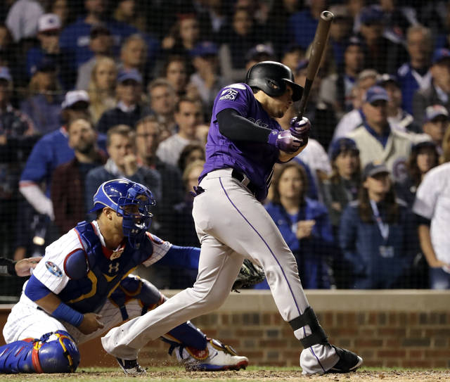 Colorado Rockies' Tony Wolters hits a one-run single against the Chicago Cubs during the 13th inning of the National League wild-card playoff baseball game Tuesday, Oct. 2, 2018, in Chicago. (AP Photo/Nam Y. Huh)