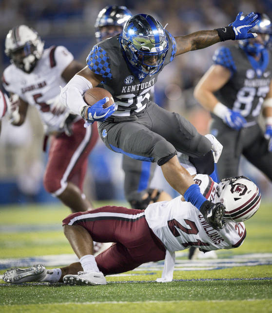 FILE - In this Sept. 29, 2018, file photo, Kentucky running back Benny Snell Jr. (26) leaps over South Carolina defensive back Jamyest Williams (21) during the first half of an NCAA college football game in Lexington, Ky. The Wildcats average 252 yards rushing per game and Snell accounts for more than half at 127.80, which is good for seventh in the nation. (AP Photo/Bryan Woolston, File)