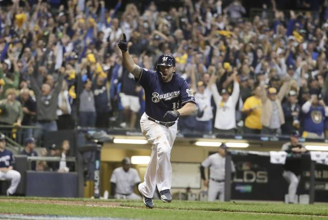 Milwaukee Brewers' Mike Moustakas hits a walk off RBI single during the 10th inning of Game 1 of the National League Divisional Series baseball game against the Colorado Rockies Thursday, Oct. 4, 2018, in Milwaukee. The Brewers won 3-2 to take a 1-0 lead in the series. (AP Photo/Morry Gash)