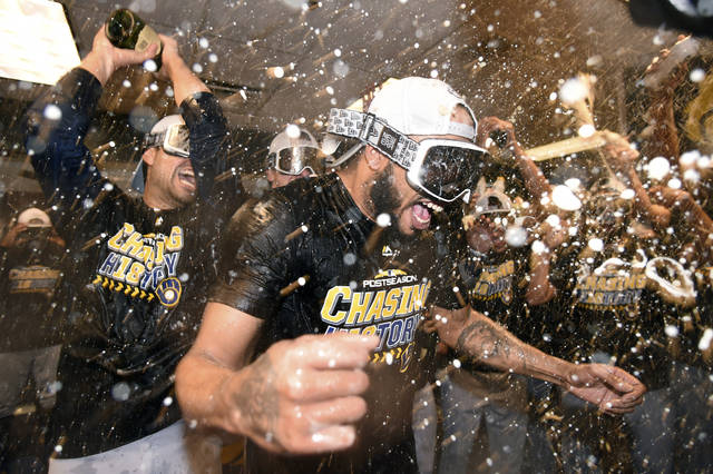 Milwaukee Brewers relief pitcher Jeremy Jeffress is doused by teammates as they celebrate in the clubhouse after Game 3 of a baseball National League Division Series against the Colorado Rockies, Sunday, Oct. 7, 2018, in Denver. The Brewers swept the series in three games and move on to the National League Championship Series. (AP Photo/John Leyba)