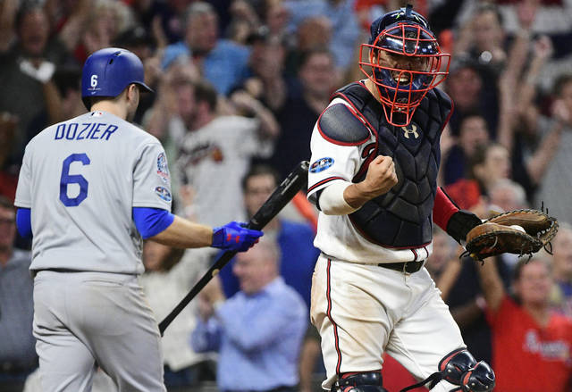 Atlanta Braves catcher Kurt Suzuki (24) celebrates the last out against Los Angeles Dodgers Brian Dozier after the ninth inning of Game 3 of MLB baseball's National League Division Series, Sunday, Oct. 7, 2018, in Atlanta. The Atlanta Braves won 6-5. (AP Photo/John Amis)