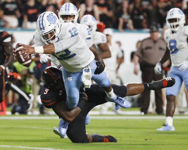 FILE - In this Sept. 27, 2018, file photo, North Carolina quarterback Chazz Surratt (12) dives in for a touchdown as he is tackled by Miami defensive lineman Gerald Willis III (9) during the first half of an NCAA college football game in Miami Gardens, Fla. Willis is second in the nation in tackles for loss with 12.5. (AP Photo/Wilfredo Lee, File)
