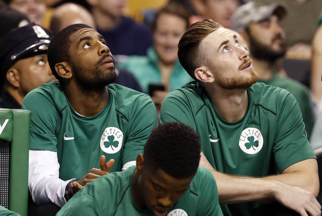 FILE - In this Oct. 9, 2017 file photo Boston Celtics' Kyrie Irving, left, and Gordon Hayward look on from the bench during the first quarter of a preseason NBA basketball game against the Philadelphia 76ers in Boston. Last season hopes were high for the Celtics in the preseason with a new-look roster that included Irving and Hayward. Five minutes into the season opener everything changed with Hayward's gruesome leg injury. It happened again late in the season with Irving was lost to knee surgery. With both back and healthy, Boston is embracing being called the presumptive favorites in the Eastern Conference. (AP Photo/Winslow Townson, file)