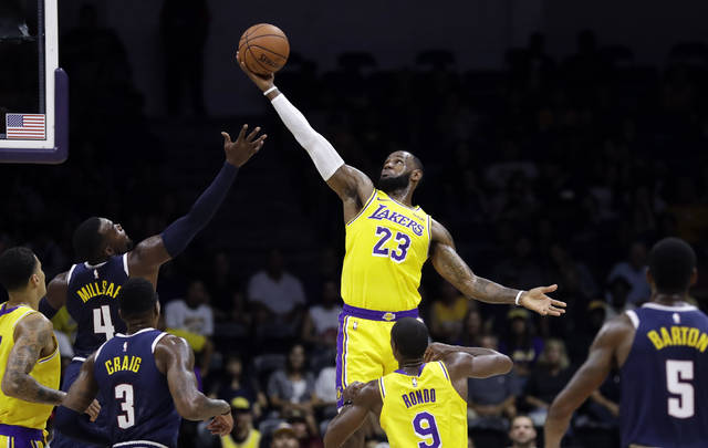 FILE - In this Sept. 30, 2018, file photo, Los Angeles Lakers forward LeBron James (23) grabs a rebound over Denver Nuggets forward Paul Millsap (4) during the first half of an NBA preseason basketball game in San Diego. The NBA's 73rd season starts Tuesday night, beginning a year where LeBron James will play for the Los Angeles Lakers. (AP Photo/Gregory Bull)