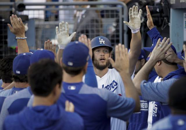 Los Angeles Dodgers' Clayton Kershaw is congratulated after scoring a run during the seventh inning of Game 5 of the National League Championship Series baseball game against the Milwaukee Brewers Wednesday, Oct. 17, 2018, in Los Angeles. (AP Photo/Jae Hong)