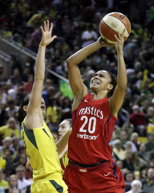 FILE - In this Sept. 9, 2018, file photo, Washington Mystics' Kristi Toliver (20) shoots over Seattle Storm's Sue Bird in the first half of Game 2 of the WNBA basketball finals, in Seattle. WNBA All-Star Kristi Toliver will be an assistant coach for player development for the NBA's Washington Wizards this season. Toliver's job was one of several changes to coach Scott Brooks' staff announced by the Wizards on Tuesday, Oct. 16, 2018, two days before they host the Miami Heat to open the season. (AP Photo/Elaine Thompson, File)