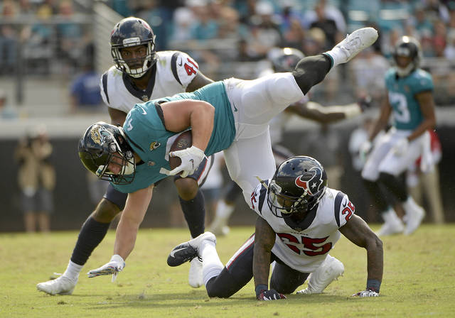 Jacksonville Jaguars running back Tommy Bohanon, center, is stopped by Houston Texans strong safety Kareem Jackson, lower right, and linebacker Zach Cunningham (41) during the second half of an NFL football game, Sunday, Oct. 21, 2018, in Jacksonville, Fla. (AP Photo/Phelan M. Ebenhack)