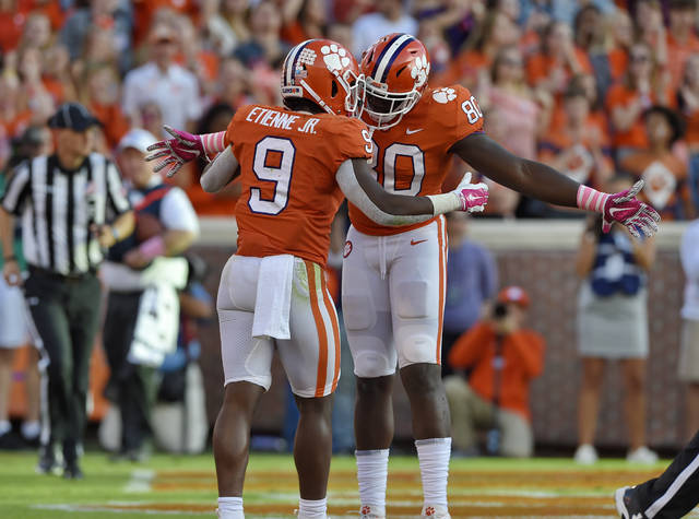 Clemson's Travis Etienne (9) celebrates with Milan Richard after scoring a touchdown during the second half of an NCAA college football game against North Carolina State, Saturday, Oct. 20, 2018, in Clemson, S.C. (AP Photo/Richard Shiro)