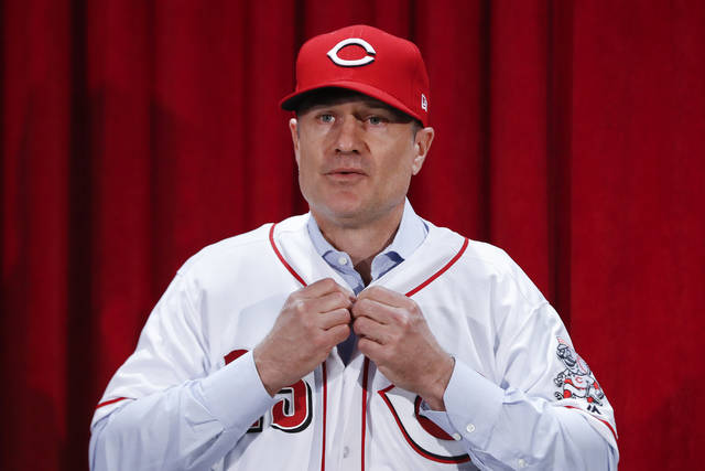 Cincinnati Reds manager David Bell puts on his number 25 jersey during a news conference, Monday, Oct. 22, 2018, in Cincinnati. Bell has been hired as manager of the Cincinnati Reds, tasked with helping turn around a team that skidded to a 67-95 record and last-place finish in the NL Central. The Reds said Sunday, Oct. 21, 2018, he has been given a three-year contract that includes a team option for 2022. (AP Photo/John Minchillo)