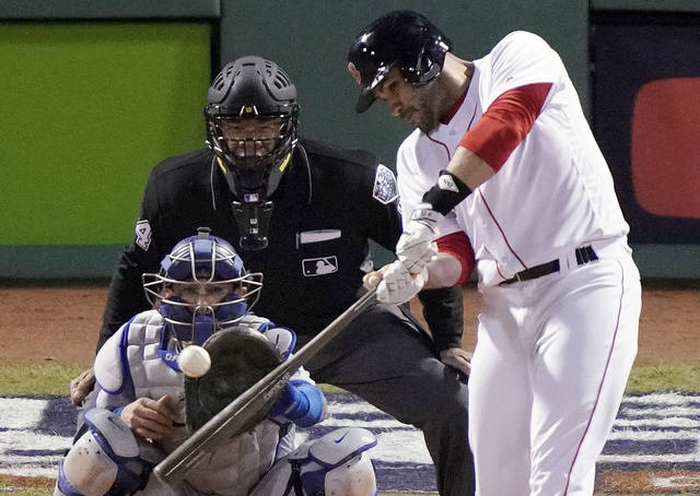 Boston Red Sox designated hitter J.D. Martinez hits a single to drive in two runs against the Los Angeles Dodgers during the fifth inning in Game 2 of the World Series baseball game, Wednesday, Oct. 24, 2018, in Boston. (AP Photo/Elise Amendola)